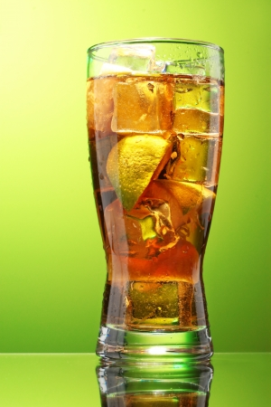 Iced tea with lemon and lime on green background photo