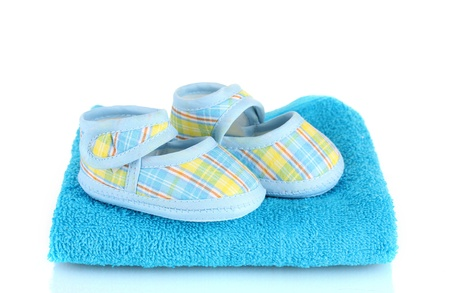 Blue baby booties on blue towel isolated on white