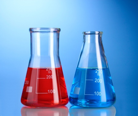 Two flasks with red and blue liquid with reflection on blue background photo