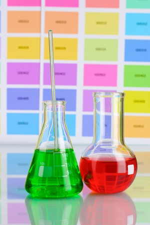 Two flasks with green and red liquid on color samples background photo