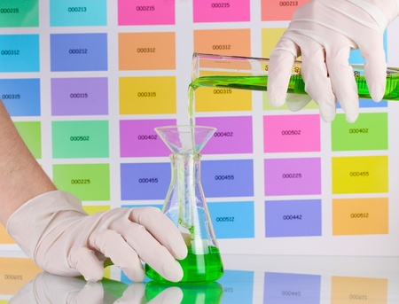transfuse: Laboratory flask and tube with green liquid in scientists hands on color samples background