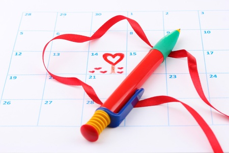 Calendar page with hearts, pen and ribbon on St.Valentines Day photo