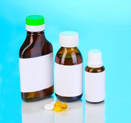 Medical bottles and tablets on blue background photo
