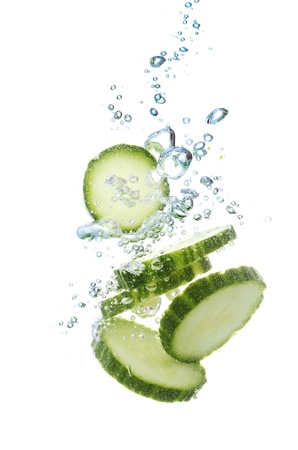 fresh sliced cucumber in water isolated on white photo