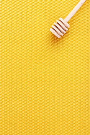 yellow beautiful honeycomb and wooden honey drizzler   photo