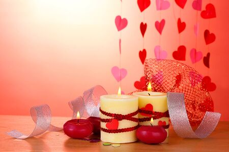 candles for Valentine's Day on wooden table on red background Stock Photo - 12217362