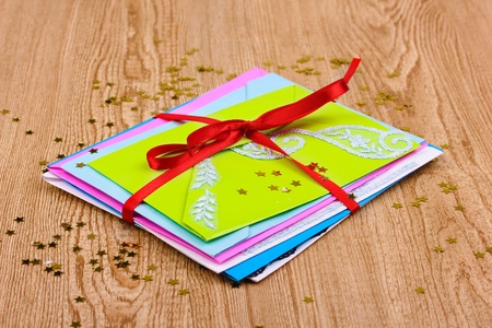 Bunch of color envelopes with ribbon and confetti on wooden background Stock Photo - 12217438