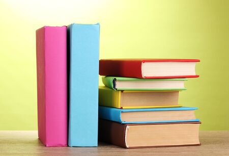 secretary tray: Stack of books on wooden table on green background