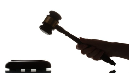 wooden gavel in hand on gray background photo