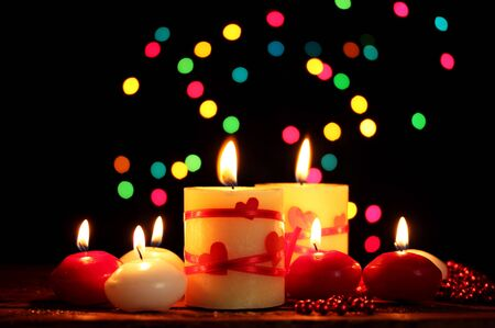 Beautiful candles on wooden table on bright background photo