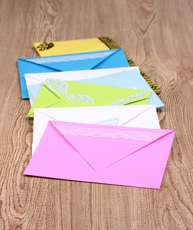 Bunch of color envelopes on wooden background photo