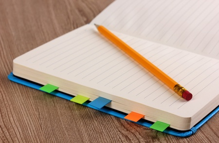 stickies: Open note book with stickies and pencil close-up on wooden background