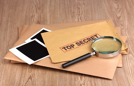 Envelopes with top secret stamp with photo papers and magnifying glass on wooden background Stock Photo - 12217671