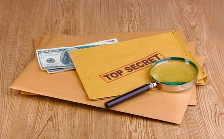 Envelopes with top secret stamp with magnifying glass and money on wooden background Stock Photo - 12217711