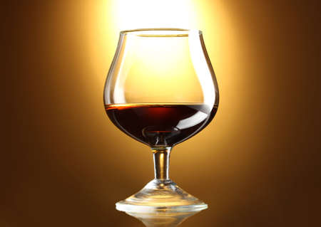 Glass of cognac on yellow background photo