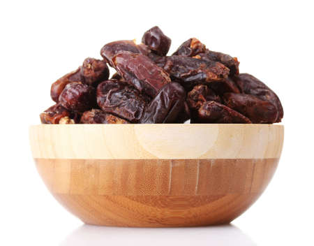 delicious dried dates in wooden bowl isolated on white photo