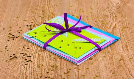 Bunch of color envelopes with ribbon and confetti on wooden background photo