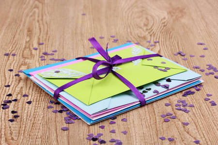 Bunch of color envelopes with ribbon and confetti on wooden background Stock Photo - 12310617