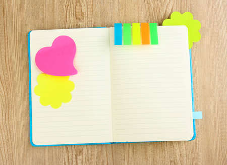 Open note book with stickies on wooden background photo