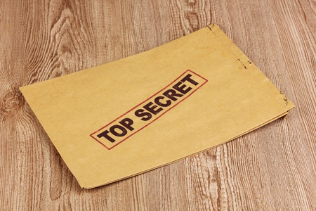 Envelope with top secret stamp on wooden background photo