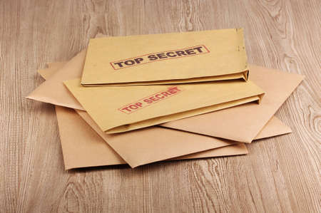 Envelopes with top secret stamp on wooden background photo