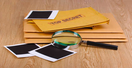 Envelopes with top secret stamp with photo papers and magnifying glass on wooden background Stock Photo - 12310659