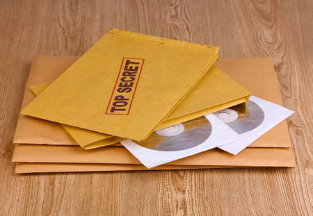 Envelopes with top secret stamp with CD disks on wooden background photo
