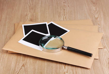 Envelopes with photo papers and magnifying glass on wooden background Stock Photo - 12310650