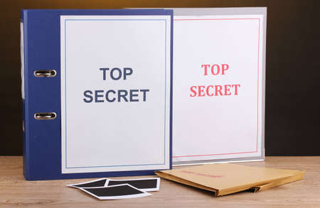 Envelopes and folders with top secret stamp and photo papers on wooden table on brown background photo