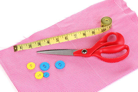 Scissors and measuring tape on fabric isolated on white photo