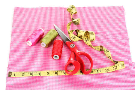 Scissors, treads and measuring tape on fabric isolated on white photo