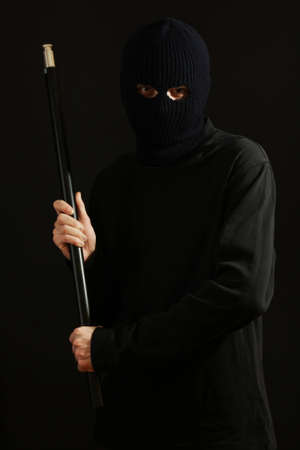 Bandit in black mask with pipe isolated on black Stock Photo - 12311130
