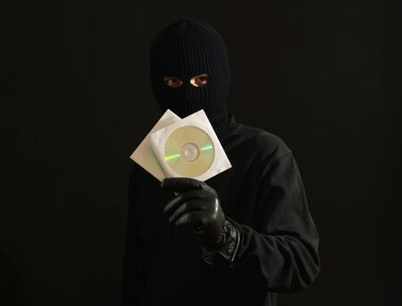 Bandit in black mask with CD disks isolated on black Stock Photo - 12311137