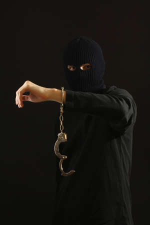 Bandit in black mask with handcuffs isolated on black photo