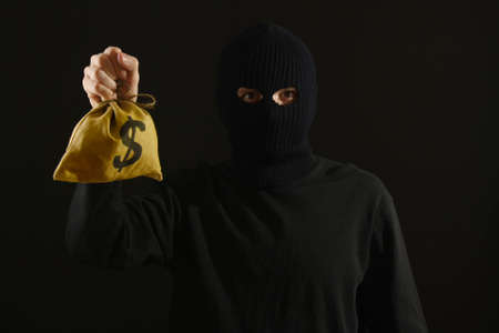 Bandit in black mask with money isolated on black photo
