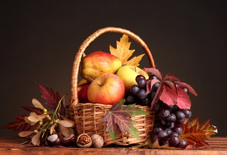 apples basket: beautiful autumn harvest in basket and leaves on brown background Stock Photo