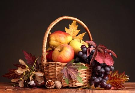 la cosecha de otoño hermosa canasta y hojas sobre fondo marrón