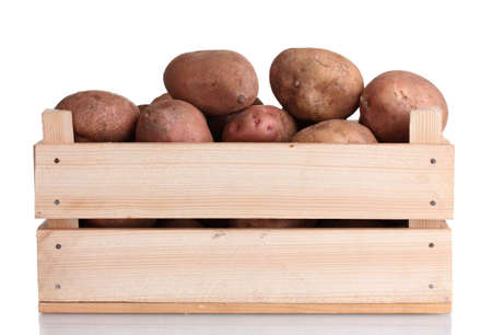 raw potatoes in a wooden box isolated on white photo