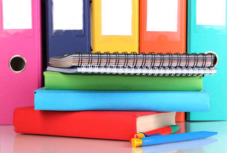 secretary tray: Bright office folders and books with stationery close-up isolated on white Stock Photo