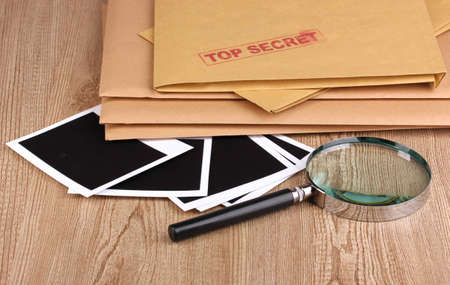 Envelopes with top secret stamp with photo papers and magnifying glass on wooden background Stock Photo - 12310453