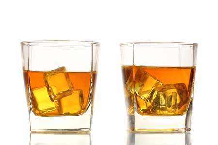 two glasses of scotch whiskey and ice isolated on white photo