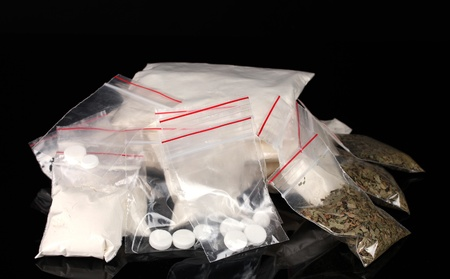 methamphetamine: Cocaine and marihuana in packages on black background
