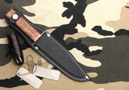 Army badges and knife on camouflage background photo