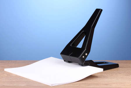 Black office hole punch with paper on blue background photo