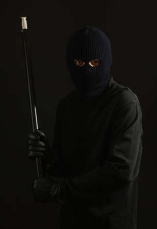 Bandit in black mask with pipe isolated on black Stock Photo - 12438645