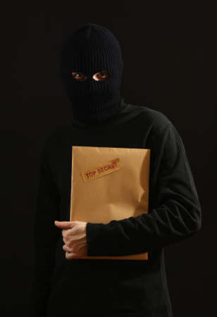 Bandit in black mask with top secret envelope isolated on black Stock Photo - 12438668