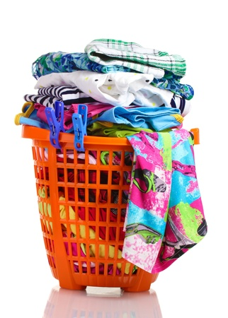messy clothes: Clothes in orange plastic basket isolated on white