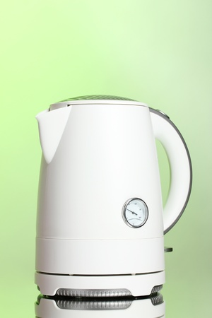 White electric kettle on green photo