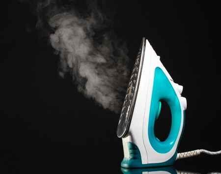 electric material: Electric iron with steam on black Stock Photo