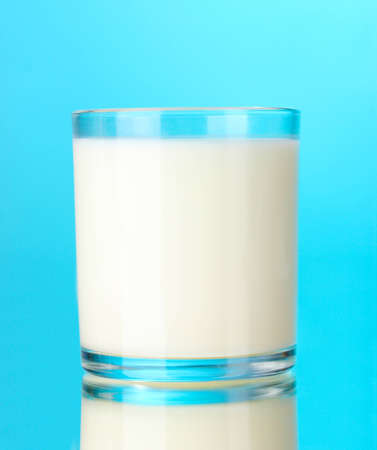 Glass of milk on blue photo